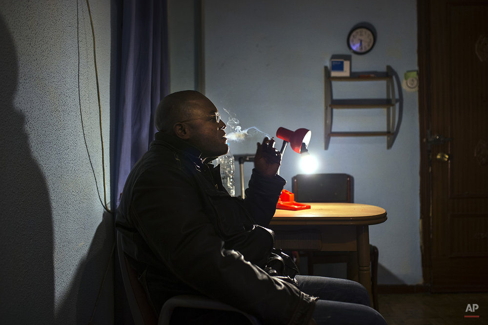 Jorge Filipe Bento, 45 years old, unemployed, from Angola with Spanish nationality, smokes as he waits for the judicial commission and the police to arrive during his eviction in Madrid, Spain, Thursday, Feb. 20, 2014. Bento purchased the euro 165,000 (US$ 225,985) apartment by taking a mortgage with Bankia bank in 2008, but ceased making payments after losing his job as a security guard in 2010. He lost the apartment to the bank and still owes euro 31,541 (US$ 43,200). The eviction was postponed the help of the Victims' Mortgage Platform (PAH). (AP Photo/Andres Kudacki)