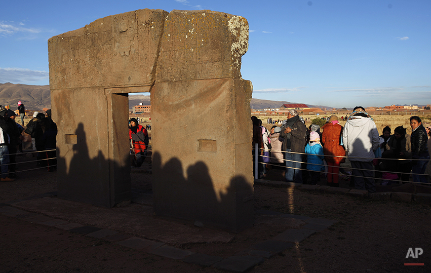 "People's shadows are cast on the ""Door of the Sun"" at the ruins of the ancient civilization of Tiwanaku during a new years ritual in the highlands in Tiwanaku, Bolivia, early Saturday, June 21, 2014. The door is believed to be part of an old solar calendar. Bolivia's Aymara Indians are celebrating the year 5,522 as well as the Southern Hemisphere's winter solstice, which marks the start of a new agricultural cycle. (AP Photo/Juan Karita)"