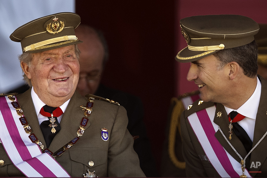 King Juan Carlos and Crown Prince Felipe, right, attend a military ceremony in San Lorenzo de El Escorial, outside Madrid, Spain, Tuesday, June 3, 2014. Spanish Prime Minister Mariano Rajoy is holding an emergency cabinet meeting to draft the legal process for King Juan Carlos to abdicate and be replaced by his son, Crown Prince Felipe. The handover cannot happen until the government crafts the mechanism for abdication and Felipe's assumption of power. The proposal is expected to pass quickly because Rajoy's center-right Popular Party has an absolute majority in Parliament.(AP Photo/Daniel Ochoa de Olza)