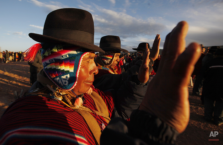 Aymara men hold up their hands to the first rays of sunlight during a new years ritual at the ruins of the ancient civilization of Tiwanaku located in the highlands in Tiwanaku, Bolivia, early Saturday, June 21, 2014. Bolivia's Aymara Indians are celebrating the year 5,522 as well as the Southern Hemisphere's winter solstice, which marks the start of a new agricultural cycle. (AP Photo/Juan Karita)