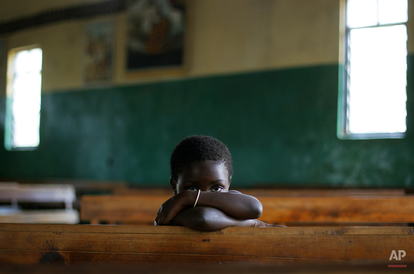 A Congolese child sits in the Kiwanja catholic church, North of Rutshuru, 75 km (48 miles) North of Goma, Congo, Sunday Aug. 5, 2012. 2012. Congo's army now controls only the city of Goma and the village of Kibumba, 10 kilometers (six miles) outside Goma. Now the rebels hold all towns going north as far as Rutshuru and are threatening to besiege Goma. The U.N. Security Council on Thursday demanded that the M23 rebel group halt any advances toward Goma. (AP Photo/Jerome Delay)