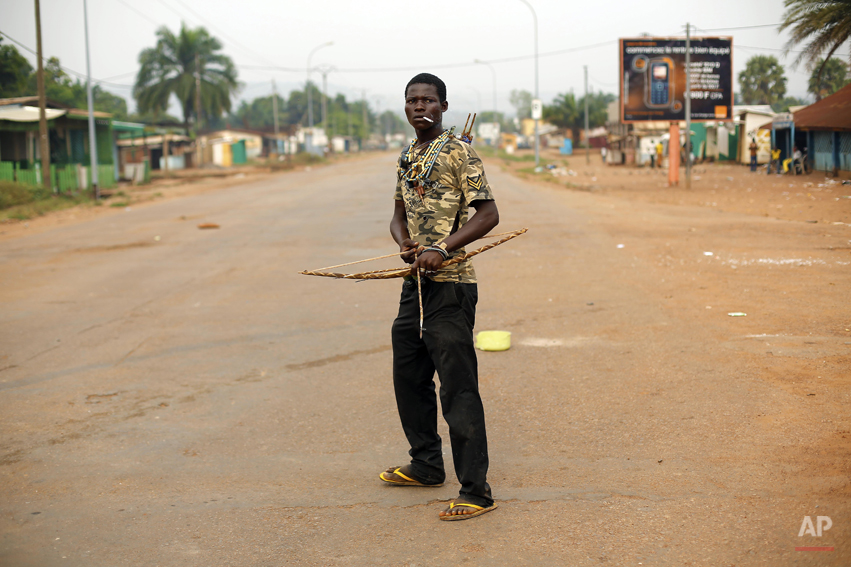 An anti-Balaka Christian militiaman holding a bow and arrow stands in, what days before, was a predominantly Muslim area of the Miskin district of Bangui, Central African Republic, Tuesday Feb. 4, 2014. All Muslim shops on the avenue leading to PK5 have been looted in the past 2 days, as anti-Balaka militiamen push back Muslim factions, opening the gates for mass looting by Christian residents. Fighting between Muslim Seleka militias and Christian anti-Balaka factions continues as French and African Union forces struggle to contain the bloodshed. (AP Photo/Jerome Delay)