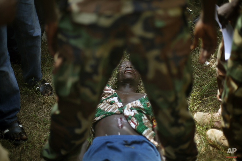 A man suspected to be a Muslim Seleka militiaman lies wounded after being stabbed by newly enlisted FACA (Central African Armed Forces) soldiers moments after Central African Republic Interim President Catherine Samba-Panza addressed the troops in Bangui, Wednesday, Feb. 5, 2014. The man died later after being lynched by hundreds of recruits using knifes, bricks and foot blows to the head. (AP Photo/Jerome Delay)