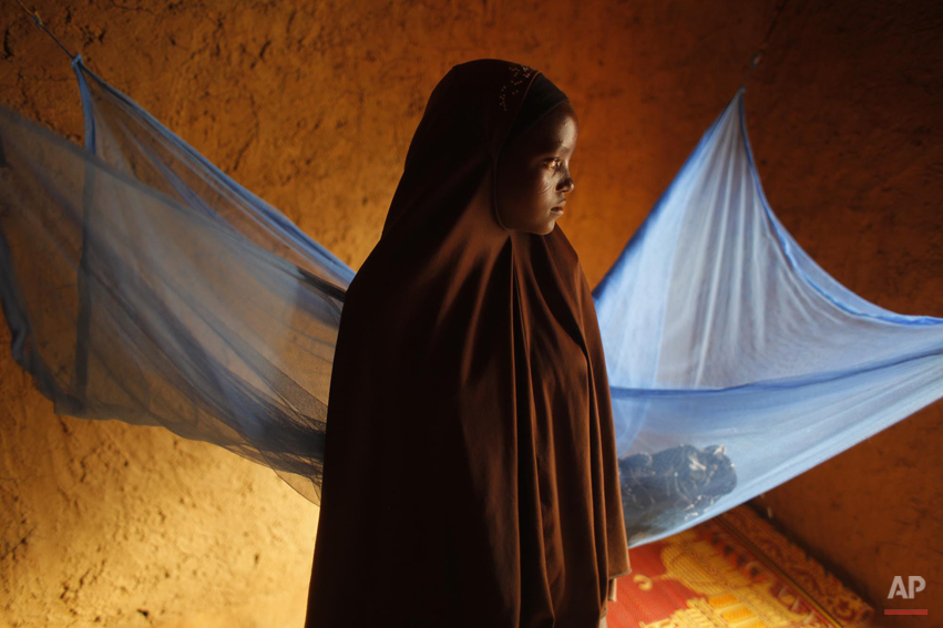 In this picture taken Wednesday, July 18, 2012, Zali Idy, 12, poses in her bedroom in the remote village of Hawkantaki, Niger. Zali was married in 2011. In January 2012, soon after she turned 12, she was carried on a bullock cart to her 23-year-old husband's home. Even during the best of times, one out of every three girls in Niger marries before her 15th birthday, a rate of child marriage among the highest in the world, according to a UNICEF survey. Now this custom is being layered on top of a crisis. At times of severe drought, parents pushed to the wall by poverty and hunger are marrying their daughters at even younger ages. A girl married off is one less mouth to feed, and the dowry money she brings in goes to feed others. (AP Photo/Jerome Delay)