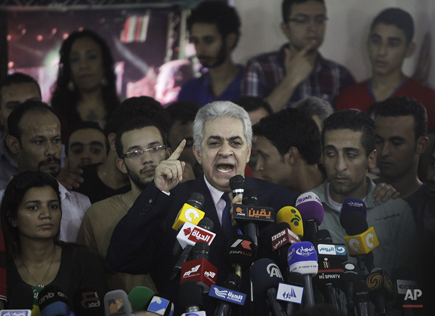 Presidential hopeful Hamdeen Sabahi talks as he is surrounded by his campaign members during a press conference at his campaign headquarters in Cairo, Egypt, Thursday, May 29, 2014. The defeated candidate in Egypt's presidential candidate has accepted defeat by the nation's former military chief, but said turnout figures announced by the government are not credible. With nearly all ballots counted, Egypt's former military chief, retired field marshal Abdel-Fattah el-Sissi, has won a crushing victory over his sole opponent Sabahi in the country's presidential election, his campaign said Thursday. But the results were stained by questions about turnout despite a robust government effort to get out the vote. (AP Photo/Amr Nabil)