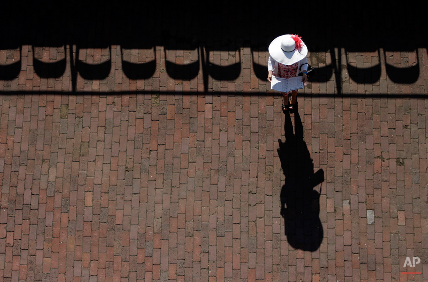 A woman checks her racing program before the 140th running of the Kentucky Derby horse race at Churchill Downs Saturday, May 3, 2014, in Louisville, Ky. (AP Photo/Charlie Riedel)
