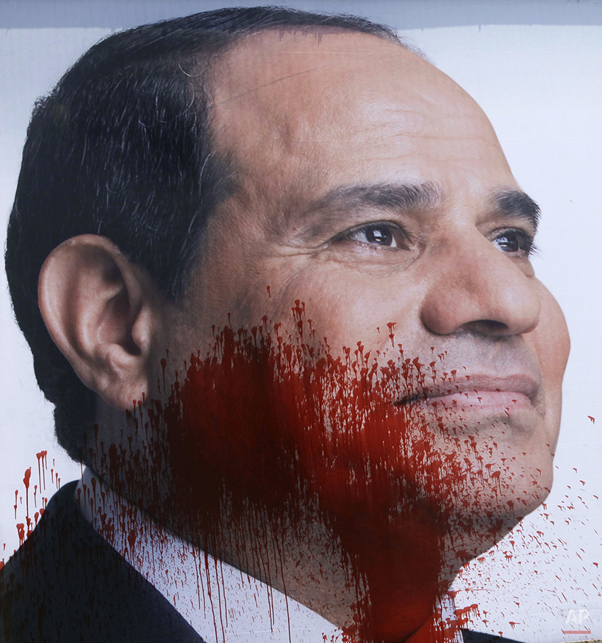 A campaign banner for presidential hopeful and retired Field Marshal Abdel-Fattah el-Sissi is seen splashed with red paint in Cairo, Egypt, Thursday, May 22, 2014. El-Sissi is running against leftist politician Hamdeen Sabahi, who placed third in the 2012 presidential election won by Morsi. Pew's poll found that Sabahi has a 35 percent favorable rating, down from 48 percent last year. (AP Photo/Amr Nabil)