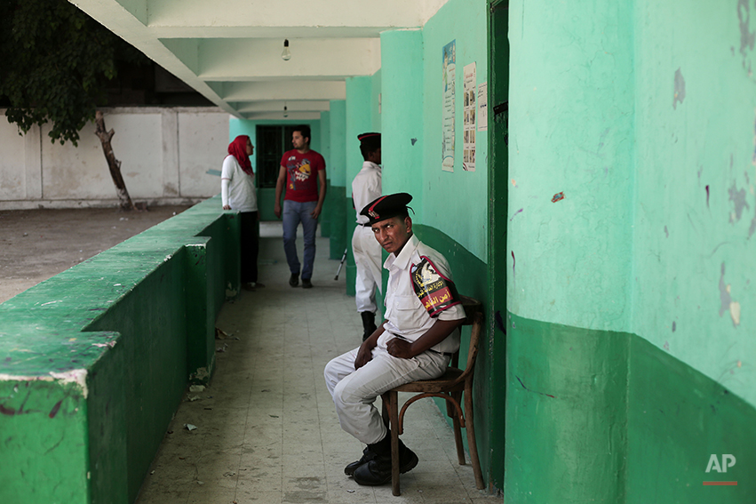 Egyptian policemen and election workers wait for voters at a polling center during the second day of presidential elections in Cairo, Egypt, Tuesday, May 27, 2014. State TV says Egypt's election commission has extended voting in the presidential election for a third day amid reported low turnout. Government officials, media and the military harangued voters to go to the polls Tuesday in what was supposed to be the final day of the vote, worried that turnout was weaker than expected. The front-runner, former army chief Abdel-Fattah el-Sissi, is trying to garner an overwhelming show of support. (AP Photo/Nariman El-Mofty)