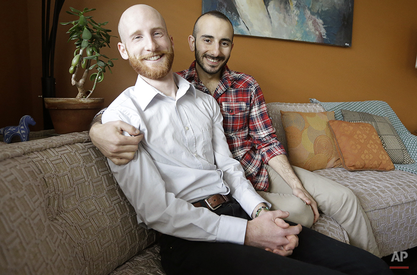 In this April 3, 2014, photo, Derek Kitchen, left, and Moudi Sbeity sit on their couch at their home, in Salt Lake City. The young couple that has become the face of gay marriage in Utah is an unlikely pair for the role. Kitchen and Sbeity were both raised in conservative religious families that shun gays, Kitchen in a Mormon home in Utah and Sbeity in a Muslim family in Lebanon. They each came out when they were 16 years old, worlds apart, and met six years later in college in Utah. They chose to become one of three couples as plaintiffs in the lawsuit challenging Utah's same-sex marriage to publicly push back against religions that oppress gays and lesbians. (AP Photo/Rick Bowmer)
