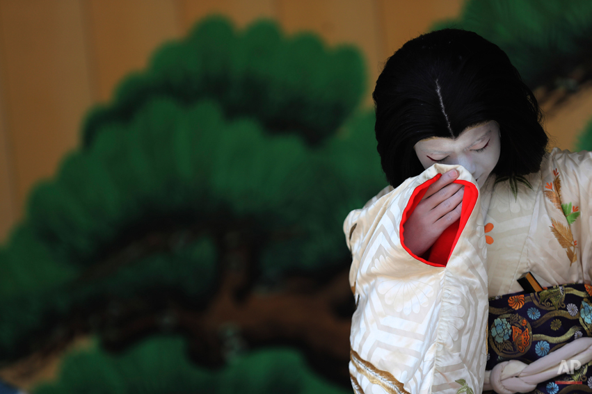 "A young boy acting as an old woman performs during a show of an amateur children kabuki theatrical company in Tokyo, Saturday, March 29, 2014. Kabuki is a Japanese classical theater performance and a male kabuki actor performs as an ""onnagata"" female impersonator. (AP Photo/Eugene Hoshiko)"