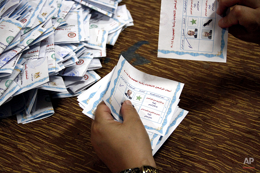 In this Wednesday, May 28, 2014 photo, an election worker displays two ballots with a check mark in front of presidential candidate Abdel-Fattah el-Sissi's name at a counting center in Cairo, Egypt. With nearly all votes counted, Egypt's former military chief has won a crushing victory over his sole opponent with more than 92 percent of the votes, according to results announced by his campaign early Thursday. The campaign of retired field marshal El-Sissi said he won 23.38 million votes, with left-wing politician Hamdeen Sabahi taking 735,285. Invalid votes were 1.07 million, or nearly 350,000 more than the number of votes for the 59-year-old Sabahi. (AP Photo/Ahmed Abdel Fattah, El Shorouk Newspaper)
