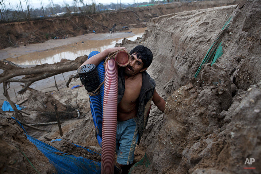 A miner carries hoses inside an illegal gold mine in La Pampa in the Madre de Dios region of Peru, Friday, May 2, 2014. People at the mine are working up to the last minute while they fear authorities will arrive any moment as part of a government crackdown on illegal gold mining since a nationwide ban took effect April 19. (AP Photo/Rodrigo Abd)