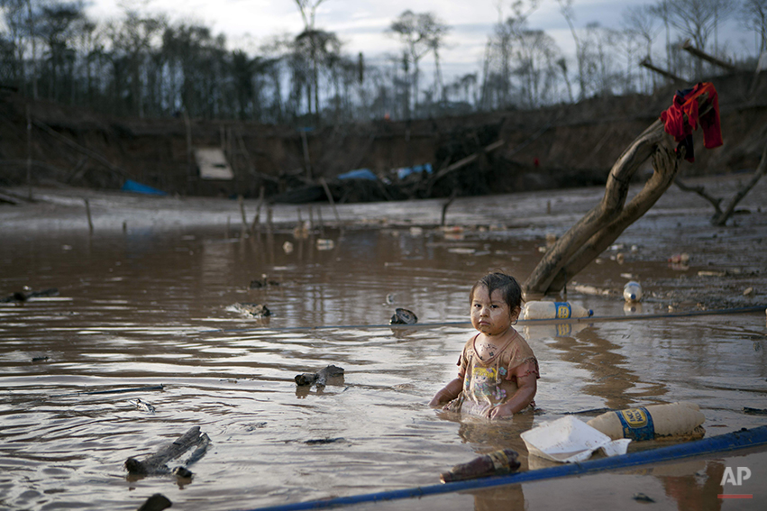 In this May 3, 2014 photo, Prisaida, 2, sits in the shallow waters of a polluted lagoon as her parents mine for gold nearby, in La Pampa in Peru's Madre de Dios region. The lagoon emerged as a result of miners bombarding the earth with jet streams of water in search of gold. The miners know they will be soon be evicted, Peru's government declared all informal mining illegal on April 19. (AP Photo/Rodrigo Abd)