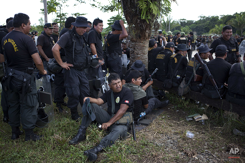 Riot police rest before the start of an operation against illegal mining in Peru's Madre de Dios region in Peru, Monday, April 28, 2014. Some 1,500 soldiers, police and marines have begun destroying illegal gold mining machinery in Peru's southeastern jungle region of Madre de Dios. Authorities began enforcing a ban on illegal mining Monday in the Huepetuhe district. They had given the state's illegal miners until April 19 to get legal or halt operations. (AP Photo/Rodrigo Abd)