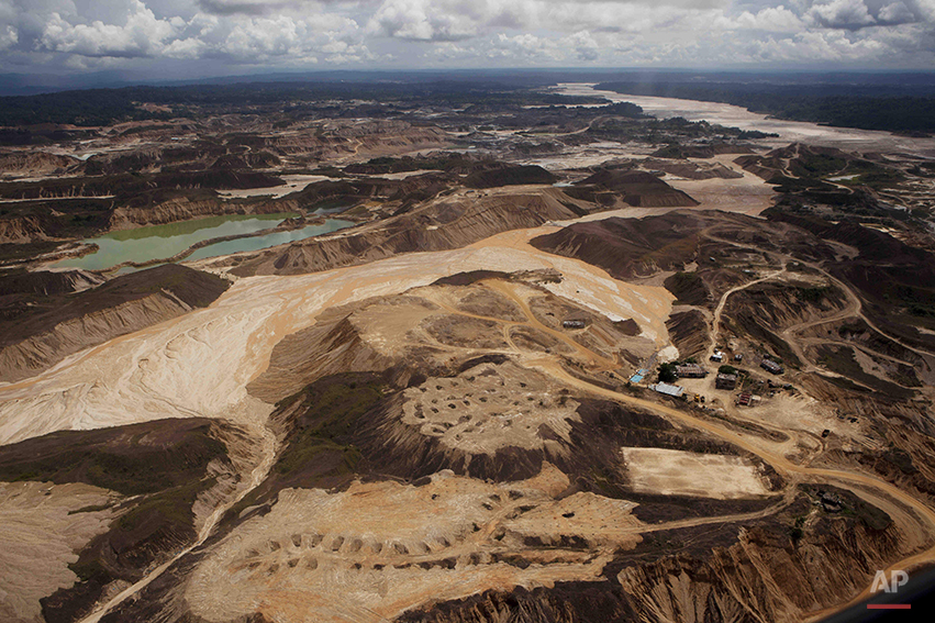 An aerial photo shows the scope of illegal mining in Huepetuhe district in Peru's Madre de Dios region in Peru, Monday, April 28, 2014. The mining uses tons of mercury and has ravaged forests and poisoned rivers. Authorities began enforcing a ban on illegal mining in the Huepetuhe district. They had given the state's illegal miners until April 19 to get legal or halt operations. (AP Photo/Rodrigo Abd)