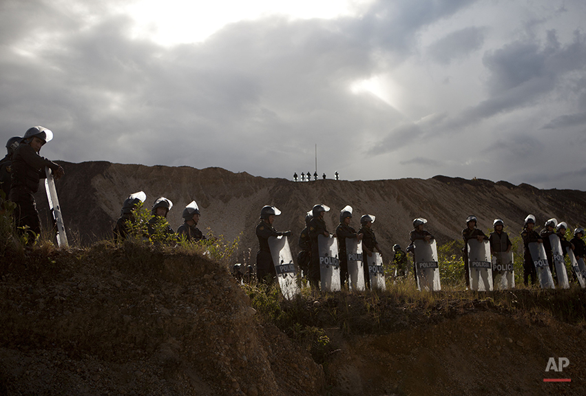 Riot police stand guard at an illegal mining operation in Huepetuhe district in Peru's Madre de Dios region in Peru, Monday, April 28, 2014. Some 1,500 soldiers, police and marines have begun destroying illegal gold mining machinery in Peru's southeastern jungle region of Madre de Dios. Authorities began enforcing a ban on illegal mining Monday in the Huepetuhe district. They had given the state's thousands of illegal miners until April 19 to get legal or halt operations. (AP Photo/Rodrigo Abd)