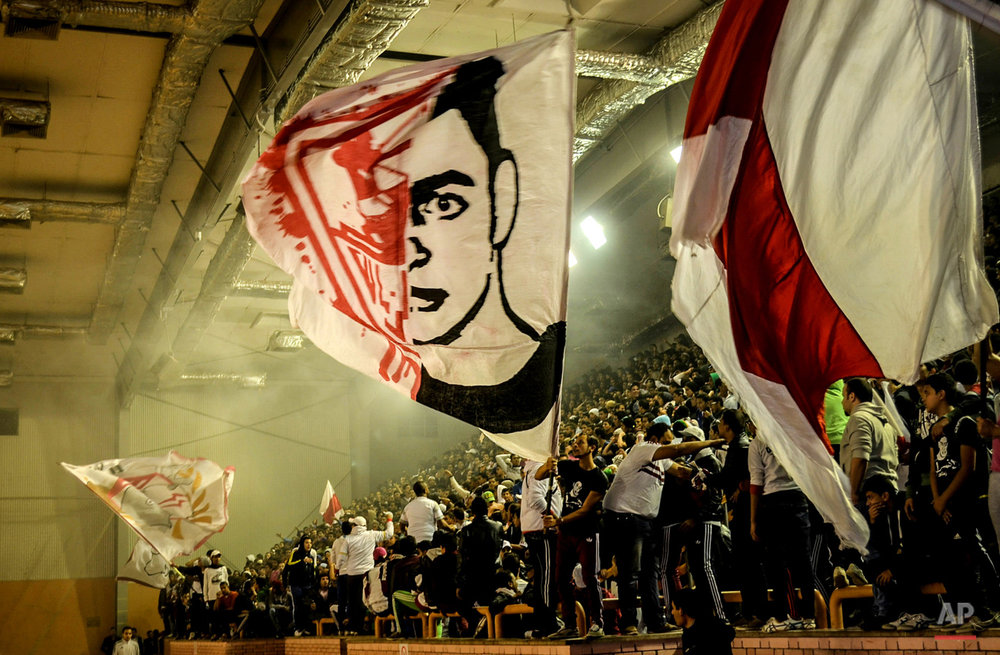 In this Dec. 24, 2013 photo, hardcore sports fans known as Ultras White Knights (UWK), wave their flags with a drawing of Amr Hussein,18, a member of the UWK who died during clashes with security forces in Sept. 2013, during a volleyball match between Zamalek and El Tayaran at the Zamalek Club, in Cairo, Egypt. Zamalek Won the match. (AP Photo/Mohammed El Raai)