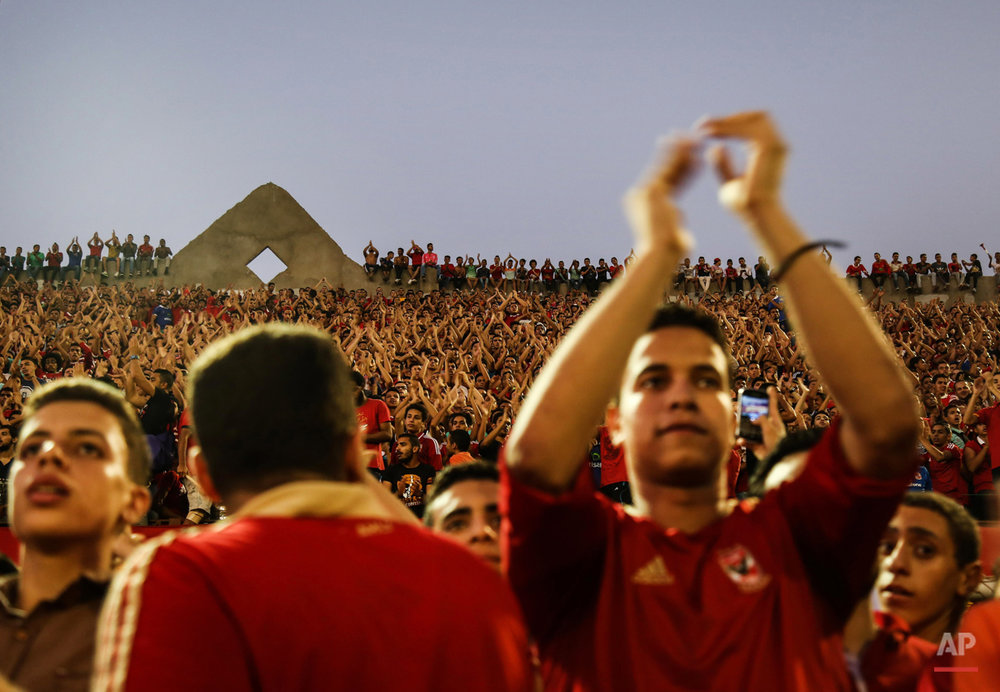 In this July 19, 2015 photo, Ultras Ahlawy, the hardcore fan base of Al-Ahly football club, cheer for team players as they train at the Al-Ahly Sporting Club, in Cairo, Egypt. Chanting slogans, carrying signs and waving flares, these eager young men who gather in Egypt could be mistaken for Arab Spring demonstrators. And in this country, the recently-banned hardcore soccer fans known as ultras have played a political role. (AP Photo/Mohammed El Raai)