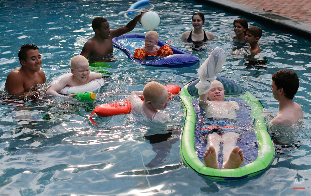 With the help of volunteer life guards, Mwigulu Magesa, Baraka Lusambo, Emmanuel Rutema and Pendo Noni swim and play in a pool in Oyster Bay, N.Y. on Monday, July 20, 2015. People with the genetic condition of albinism, characterized by a lack of pigment, are often referred to in Tanzania as ghosts, or zero zero, which in Swahili signifies someone who is less than human. (AP Photo/Julie Jacobson)