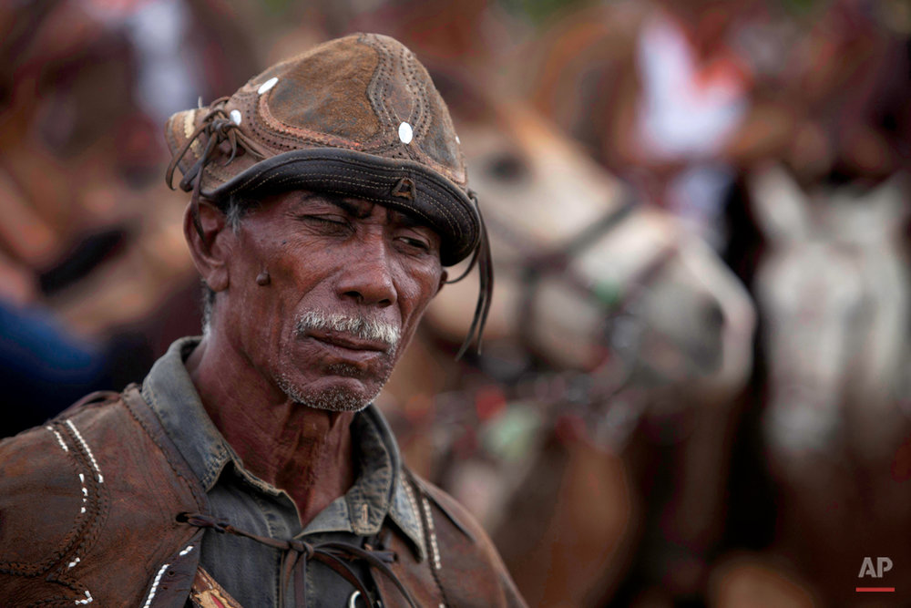 """In this July 24, 2015 photo, cowboy Joao do Dito arrives to the annual Catch the Bull competition known as the """"Pega do Boi"""" in Serrita, in Brazil's Pernambuco state. The 66-year-old lost the use of his right eye while competing one year, and now comes to watch others compete. (AP Photo/Eraldo Peres)"""