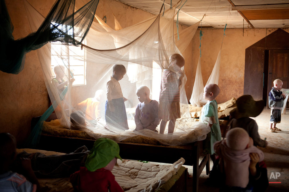 Children play under mosquito netting inside a dormitory of the Kabanga Protectorate Center, housed in a walled compound for the Kabanga Primary School, in Kabanga, Tanzania on Monday, Aug. 27, 2012. The dorms are overcrowded as more people with albinism have been sent to live at the center by the government for their own safety. In danger from witch doctors, Tanzania's albinos hope their government will start to offer more help. (AP Photo/Jacquelyn Martin)