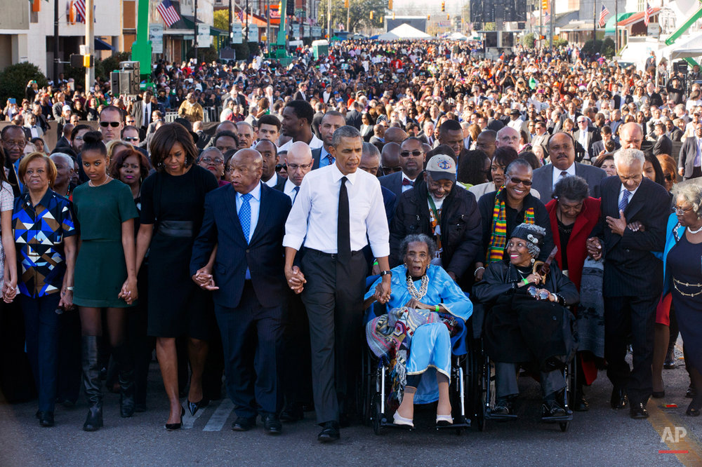 "President Barack Obama, center, walks as he holds hands with Amelia Boynton Robinson, who was beaten during ""Bloody Sunday,"" as they and the first family and others including Rep. John Lewis, D-Ga,, left of Obama, walk across the Edmund Pettus Bridge in Selma, Ala. for the 50th anniversary of ìBloody Sunday,"" a landmark event of the civil rights movement, Saturday, March 7, 2015. From front left are Marian Robinson, Sasha Obama. first lady Michelle Obama. Obama, Boynton and Adelaide Sanford, also in wheelchair. (AP Photo/Jacquelyn Martin)"