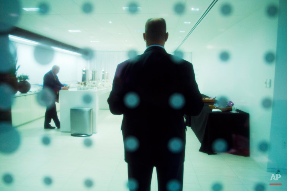 A Secret Service Agent is seen through tinted and patterned glass as he stands in front of the door to a room where President Barack Obama was meeting with leading CEOs to discuss ways to promote the economy and create jobs during his last two years in office, Wednesday, Dec. 3, 2014, at the Business Roundtable Headquarters in Washington. (AP Photo/Jacquelyn Martin)