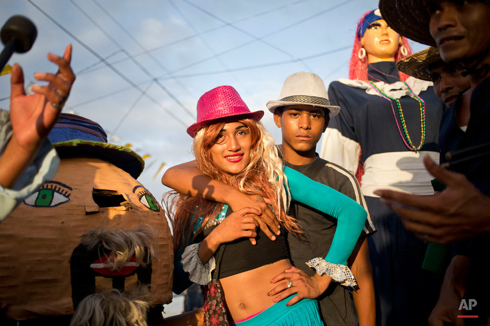 "In this Aug. 7, 2015 photo, two men dressed as a couple pose for a photo next to traditional dolls known as a ""Gigantona,"" right, and a ""Pepe Cabezon,"" left, during Managua's patron saint, Santo Domingo de Guzman's celebration, in Managua, Nicaragua. The dolls dance around as fellow performers play on drums and shout out ribald poems for a small fee. (AP Photo/Esteban Felix)"