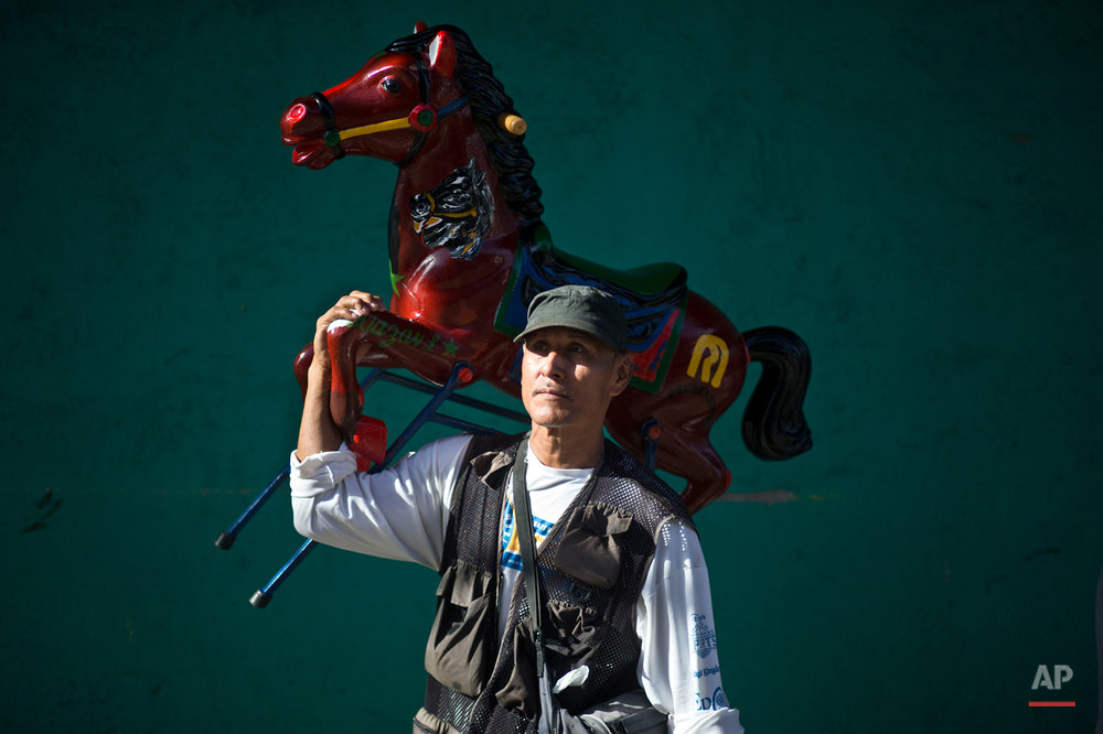 In this Aug. 4, 2015 photo, a street photographer poses for a portrait with his wooden horse during Managua's patron saint, Santo Domingo de Guzman's celebration, in Managua, Nicaragua. His clients are mostly devotees who want a keepsake of the feast and he charges them about $2 per photo. (AP Photo/Esteban Felix)