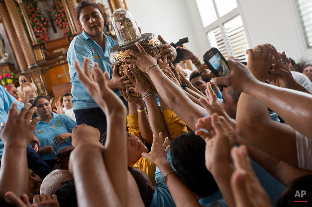 In this July 31, 2015 photo, people reach to touch an image of Santo Domingo de Guzman at Las Sierritas parish church, in Managua, Nicaragua. The 8-centimeter (just a little over 3 inches) tall statute of the saint is protected by a glass bell and carried through throngs of devotees during the celebration. (AP Photo/Esteban Felix)