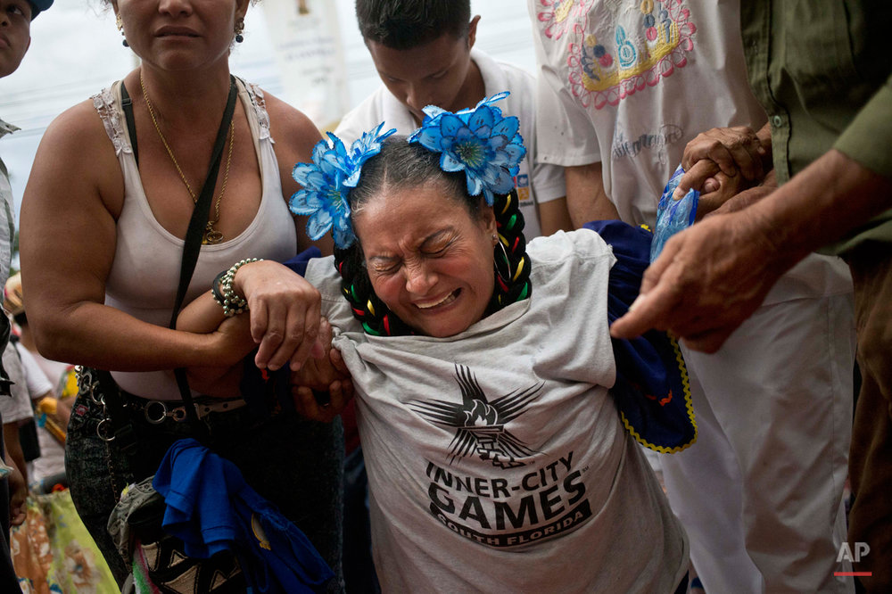 In this Aug. 10, 2015 photo, a ìpromesanteî or devotee, grimaces in pain as she moves towards the Las Sierritas parish church, on her knees, assisted by relatives during Managua's patron saint, Santo Domingo de Guzman's celebration, in Managua, Nicaragua. The 10 days of festivities have their roots in the 1885 discovery of the tiny statute of Santo Domingo de Guzman, also known as St. Dominic de Guzman, the founder of the Dominican religious order. (AP Photo/Esteban Felix)