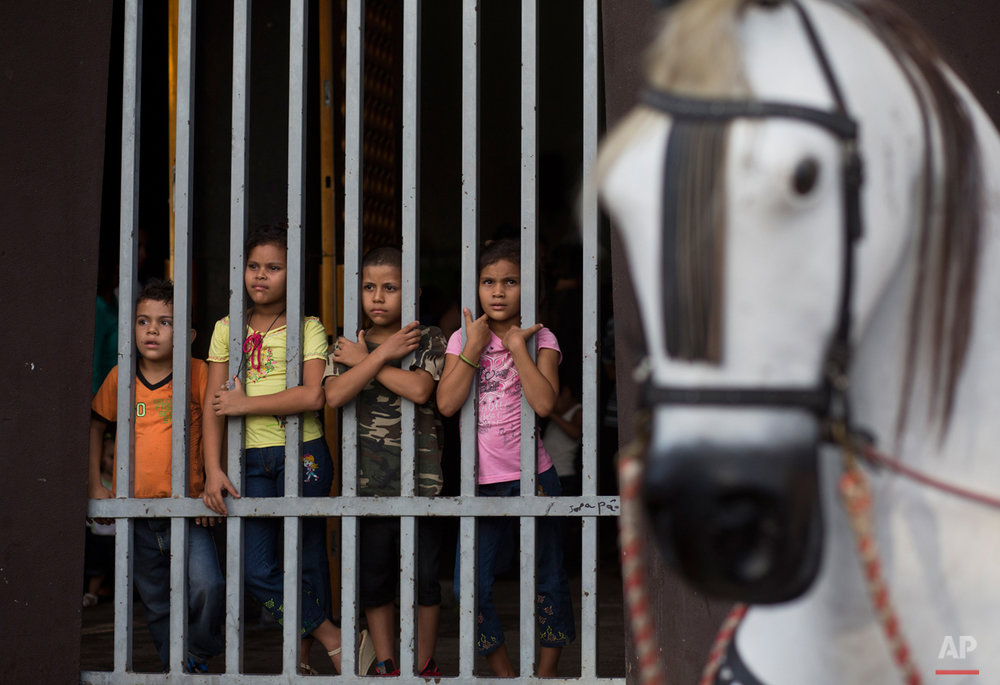 In this Aug. 4, 2015 photo, a group of children stands inside the Santo Domingo church during Managua's patron saint, Santo Domingo de Guzman's celebration, in Managua, Nicaragua. Nicaraguans of all classes and from all walks of life, from small children to the elderly, come out in full force to celebrate the feast. (AP Photo/Esteban Felix)