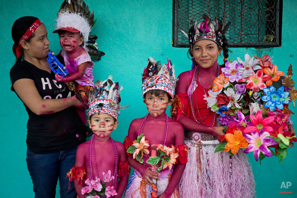 In this Aug. 10, 2015 photo, the Lopez family, with their  bodies covered with red paint, pose for a picture during a Managua's patron saint, Santo Domingo de Guzman's celebration, in Managua, Nicaragua. For more than 30 years the three generations of the Lopez family have been participating in the celebrations of the feast of Santo Domingo. (AP Photo/Esteban Felix)