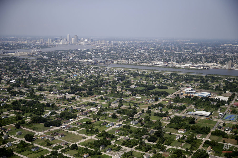 This July 29, 2015 aerial photo shows empty lots and mostly new buildings in the Lower 9th Ward section of New Orleans, foreground. Ten years after Katrina, New Orleans remains a work in progress, aiming to reverse historic racial and economic injustices. (AP Photo/Gerald Herbert)