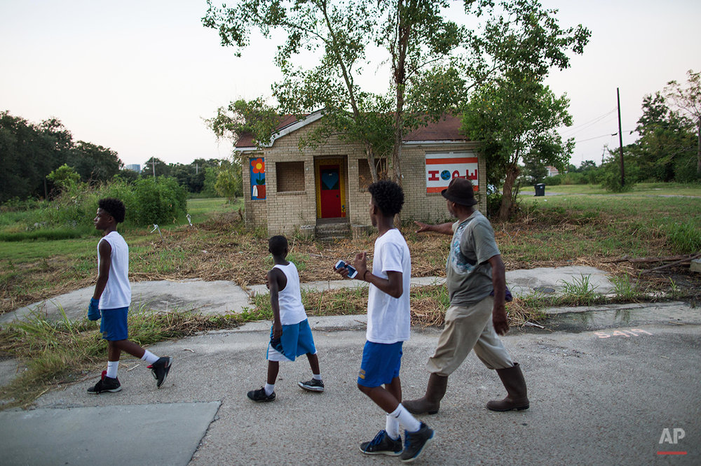 Harry Sims, 62, walks past a blighted building which was destroyed by Hurricane Katrina in the Lower 9th Ward of New Orleans on the way to a park for warm up exercises with his boxing students, Friday, Aug. 14, 2015. Sims started the boxing club to keep kids out of trouble in the neighborhood. (AP Photo/Max Becherer)