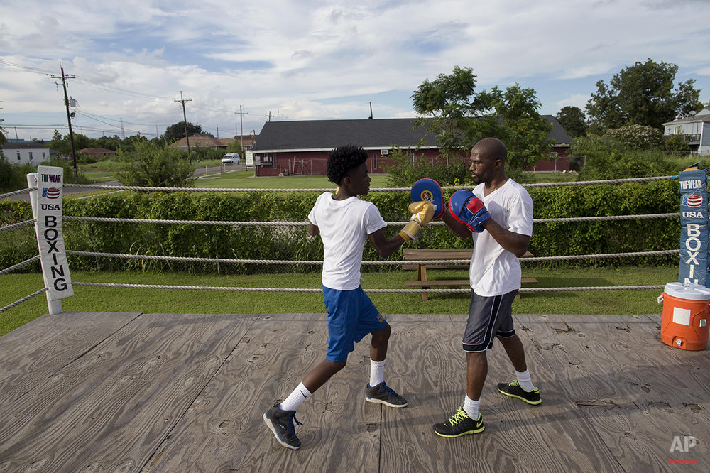 Darien Ford, 43, right, spars with Deshane Sims, 14, at the Running Bear Boxing Club in the Lower 9th Ward in New Orleans, Monday, Aug. 17, 2015. The boxing club is run by a resident of the Lower 9th Ward, Harry Sims, 62, to keep kids out of trouble in the neighborhood. (AP Photo/Max Becherer)