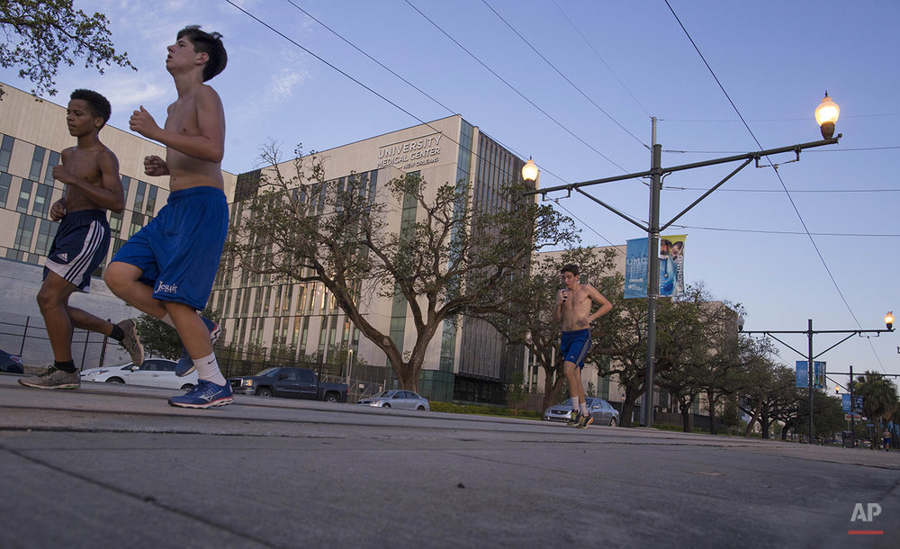 "Students from Jesuit High School of New Orleans take an early morning run past the newly opened $1.1 billion University Medical Center, built to replace Charity Hospital, which was flooded during Hurricane Katrina in New Orleans, Saturday, Aug. 15, 2015. People who talk about a renaissance in the city speak in the same breath about those didn't recover. The ""New"" New Orleans is whiter and more expensive to live in. African-American neighborhoods across the city still struggle, especially the chronically neglected Lower 9th Ward, a center of black home ownership before the floodwalls failed. And the murder rate is rising again. (AP Photo/Max Becherer)"