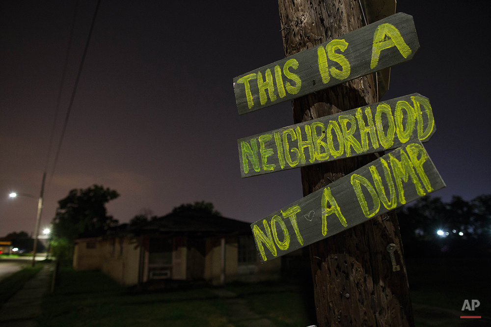A hand made sign at North Rocheblave and Lamanche Streets in the Lower 9th Ward of New Orleans attempts to thwart the illegal dumping of tires and industrial waste, Friday, Aug. 14, 2015. (AP Photo/Max Becherer)