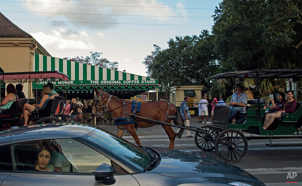 Tourists in cars and horse drawn buggies pass the Cafe du Monde in the French Quarter of New Orleans, Saturday, Aug. 15, 2015. New Orleans is nearly three centuries old, mixing African-American, French, Spanish and Caribbean traditions to create unique forms of music, food and culture found nowhere else in America. (AP Photo/Max Becherer)