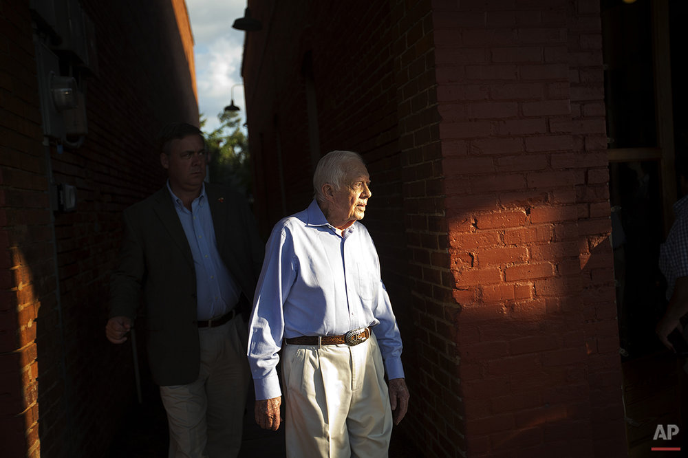 Former President Jimmy Carter leaves a reception in his hometown of Plains, Ga., Saturday, Aug. 22, 2015. As Carter undergoes treatment for cancer that has spread to his brain, the town of less than 800 people is ready to support him. Friends say they hope yard signs, well wishes and entertainment will keep the 90-year-old Carter's spirits up. (AP Photo/David Goldman)