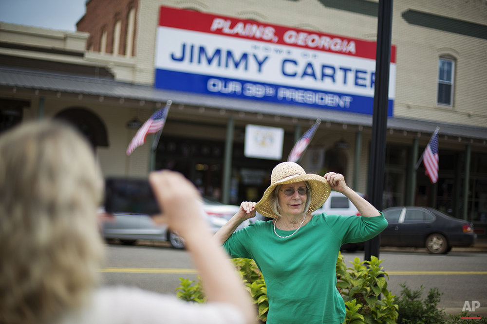 Paula McNeill, right, of Valdosta, Ga., has her photo taken by Melinda Groover, of Birmingham, Ala., as they visit the hometown of former President Jimmy Carter in Plains, Ga., Sunday, Aug. 23, 2015. Carter's 1976 election to the presidency made Plains a tourist destination. The one-block business district specializes in Carter political memorabilia and peanut souvenirs. (AP Photo/David Goldman)