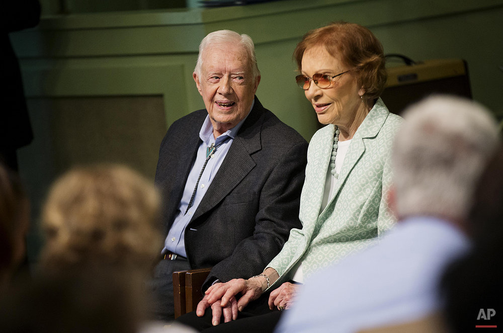 Former President Jimmy Carter, left, sits with his wife Rosalynn as they pose for photos after Carter taught Sunday School class at Maranatha Baptist Church in his hometown Sunday, Aug. 23, 2015, in Plains, Ga. The 90-year-old Carter gave one lesson to about 300 people filling the small Baptist church that he and his wife, Rosalynn, attend. It was Carter's first lesson since detailing the intravenous drug doses and radiation treatment planned to treat melanoma found in his brain after surgery to remove a tumor from his liver. (AP Photo/David Goldman)