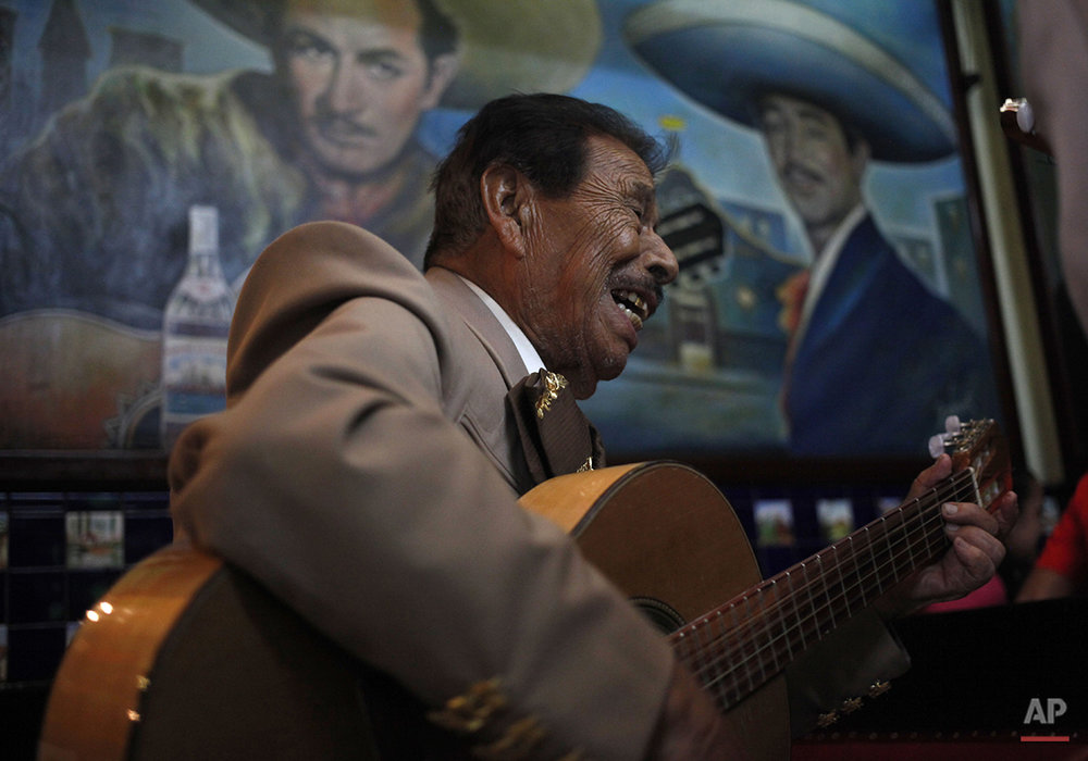 In this July 29, 2015 photo, 90-year-old mariachi Jose Jesus performs inside the Salon Tenampa bar and restaurant in Garibaldi Plaza in Mexico City. The mural features late Mexican mariachi legends Pedro Infante, left, and Javier Solis. (AP Photo/Sofia Jaramillo)
