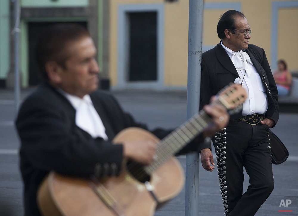 "In this Aug. 6, 2015 photo, musicians wait to be hired in Garibaldi Plaza, a downtown square famous for open-air performances by strolling musicians in Mexico City. ""This is considered to be the home of mariachi,"" and among the oldest on the plaza, said Cesar Coronado Ferrer, a singer who has performed at the nearby Salon Tenampa for 30 years. (AP Photo/Sofia Jaramillo)"