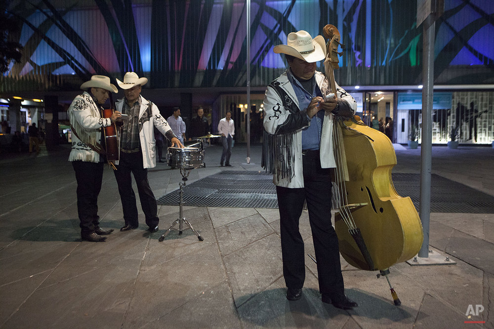 In this Aug. 6, 2015 photo, a trio of musicians waits for clients to hire them in Garibaldi Plaza in Mexico City. The downtown square is famous for open-air performances by strolling musicians. (AP Photo/Sofia Jaramillo)
