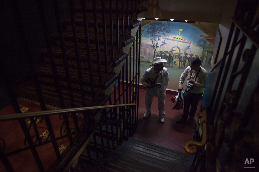 "In this Aug. 21, 2015 photo, a jarocho musician walks up the stairs to the terrace of the Tenampa Salon restaurant and bar in Mexico City. ""Here, visitors want the experience of classic Mexico in the music, the food, and the drinks,"" said bartender Abraham Manilla. ""At least four songs were written here in the restaurant."" (AP Photo/Sofia Jaramillo)"
