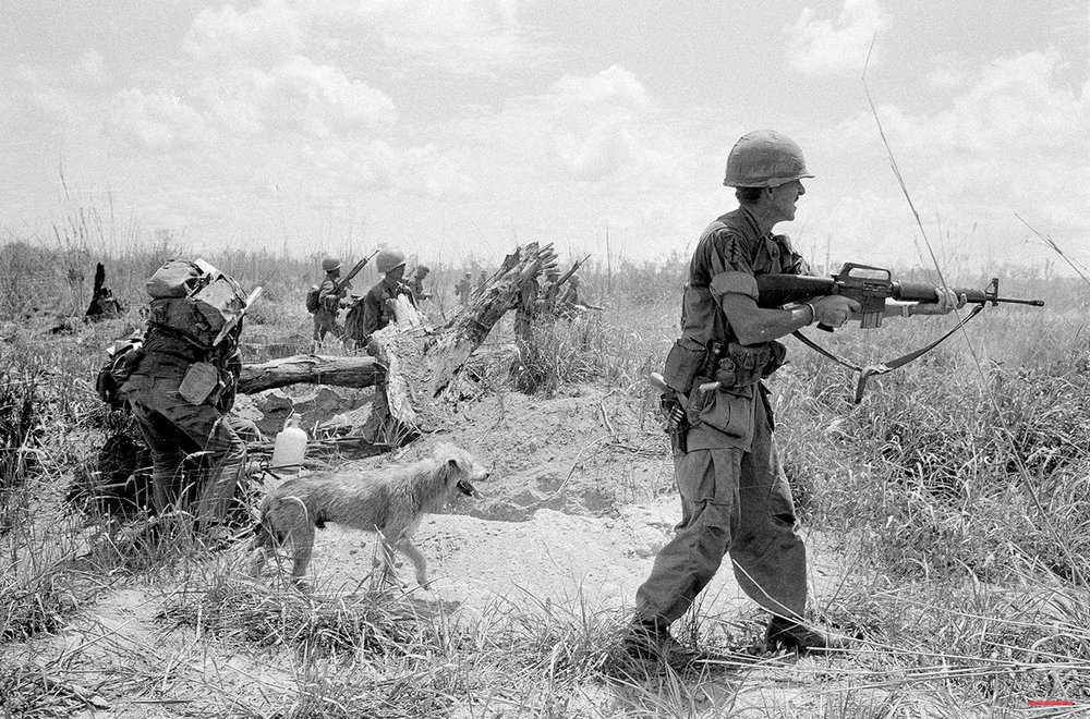 U.S. Adviser Lt. Col. Burr M. Willey, of Ayer, Mass., fired his rifle as he moved up Route 13 with a South Vietnamese army unit toward An Loc, besieged provincial capital north of Saigon. In this scene in Vietnam, May 19, 1972, Willey was followed by his faithful dog Moose and South Vietnamese troops. On June 19, the colonel and his dog were killed during a rocket attack in the area along Route 13. (AP Photo/Nick Ut)