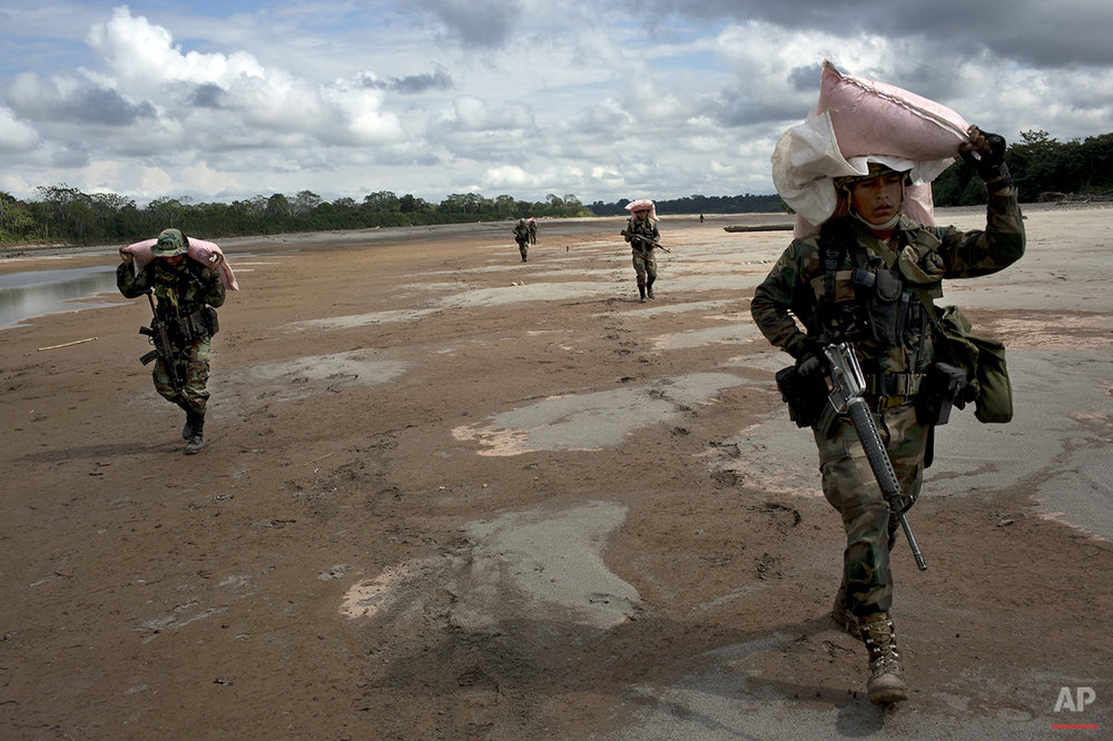 In this July 28, 2015 photo, counternarcotics special forces officers carry sacks of ammonium nitrate explosives to crater a clandestine airstrip in the Peruvian jungle, on the shores of the Palcazu River, near Ciudad Constitucion, Peru. Police say that the runways are used to move more than a metric ton of cocaine a day to Bolivia on small planes. (AP Photo/Rodrigo Abd)