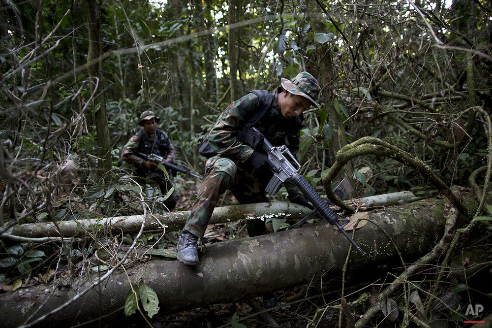 In this July 31, 2015 photo, counternarcotics special forces trek in the jungle after cratering a clandestine airstrip used by drug traffickers near Ciudad Constitucion, Peru. The airstrip can be repaired within a few days, sometimes less, depending on the traffickers. (AP Photo/Rodrigo Abd)