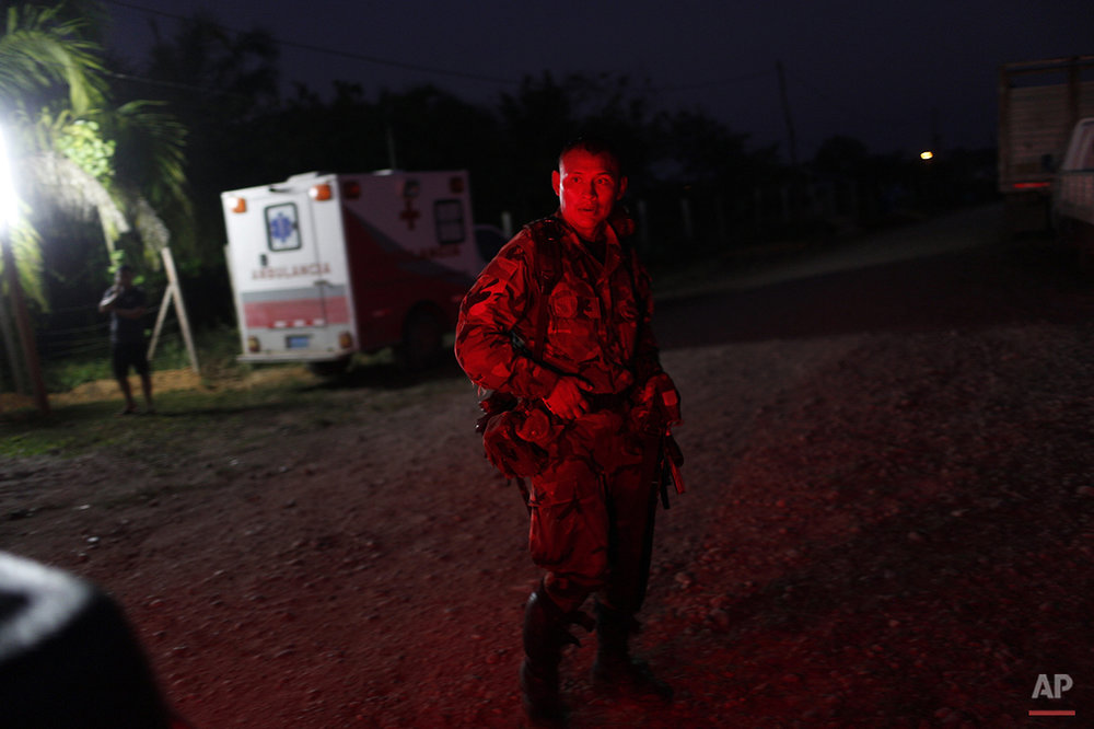 "In this July 31, 2015 photo, a counternarcotics special forces police officer is illuminated by the lights of a pick-up truck at his base Ciudad Constitucion, Peru. He has just arrived from cratering a clandestine airstrip used by drug smugglers in the Peruvian jungle. Blasting craters in runways only briefly interrupts the so-called ""air bridge."" (AP Photo/Rodrigo Abd)"